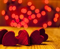 Red wooden hearts with lights in the background. Red wooden hearts on wooden table with red lights in the background Royalty Free Stock Photo