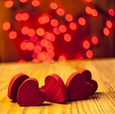 Red wooden hearts with lights in the background. Red wooden hearts on wooden table with red lights in the background Royalty Free Stock Photos