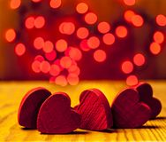 Red wooden hearts with lights in the background. Red wooden hearts on wooden table with red lights in the background Stock Photo