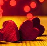 Red wooden hearts with lights in the background. Red wooden hearts on wooden table with red lights in the background Royalty Free Stock Image