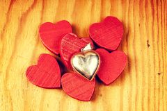 Red wooden hearts with lights with silver pendant in the background. Red wooden hearts on wooden table with silver pendant in the background Stock Photo