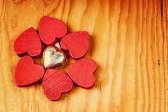 Red wooden hearts with lights with silver pendant in the background. Red wooden hearts on wooden table with silver pendant in the background Stock Images