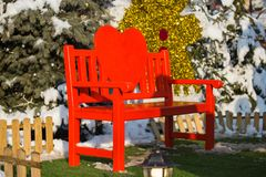 Red wooden holiday lovely Christmas decorative love bench in the. Park with nature and snow in the winter and heart gingerbread decoration green grass New Year Stock Photography