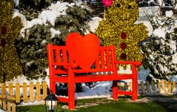 Red wooden holiday lovely Christmas decorative love bench in the. Park with nature and snow in the winter and heart gingerbread decoration happy sunny New Year Stock Photo