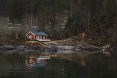 Red wooden house near the lake against the background of the forest and the mountains. Reflection in water royalty free stock image
