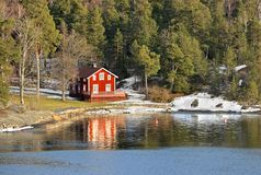 Red wooden house on shore Stock Images