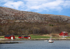 Red wooden houses on rocky coast. Traditional small Norwegian village with red wooden houses on rocky coast and small fishing boat nearby Royalty Free Stock Photo