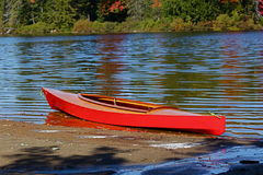 Red wooden kayak on a lake. A red wooden kayak is in the water close to shore on a lake Stock Images