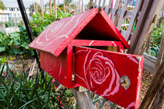 Red Wooden Letterbox with a Floral  Pattern. A red wooden letterbox with a white painted floral patern on its roof and door. Found in a community garden in St Stock Photo