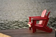 Red Wooden Lounge Chair on Brown Boardwalk Near Body of Water during Daytime Stock Photography