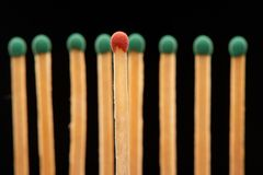 Red wooden match standing in front of eight green matches Royalty Free Stock Image