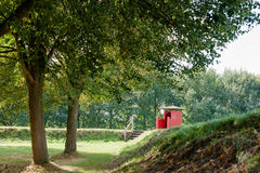 Red, wooden, old guardhouse near the canal of the fortress. Stock Photos