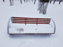 Wooden Park Bench Covered By Snow In The Park royalty free stock photo