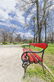 Red wooden park bench at a park Stock Photos