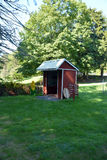 Red Wooden Produce Stand on Farm. A red wooden produce stand sits in the yard of a country farm Royalty Free Stock Photography