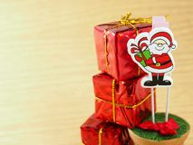 Red  wooden Santa Claus, decorated on handmade paper clip with red gift box Royalty Free Stock Image
