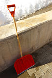 Red wooden shovel leaning against the wall Stock Images