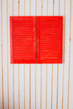 Red wooden shutters on a white wall Stock Photo