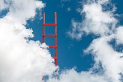Red Stairway To Heaven. The Road To Success. Achievement Of Goals Career Concept. A red wooden staircase against a blue cloud of a symbol of success and Stock Photos
