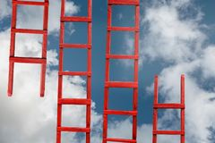 Red Stairway To Heaven. The Road To Success. Achievement Of Goals Career Metaphor. A red wooden staircase against a blue cloud of a symbol of success and Royalty Free Stock Photos