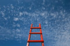 Red Staircase Rests Against Blue Sky. Development motivation Career Growth Concept. Red wooden staircase against the blue sky Stock Images