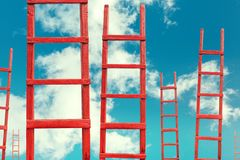 Red Wooden Stairway to Heaven. Road To Success. Achievement Of Goals Career Concept. A red wooden staircase against a blue cloud of a symbol of success and Stock Photo