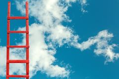 Red Wooden Stairway to Heaven. Road To Success. Achievement Of Goals Career Metaphor. A red wooden staircase against a blue cloud of a symbol of success and Royalty Free Stock Photos