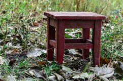 Red wooden stool outdoors. Horizontal frame royalty free stock photos