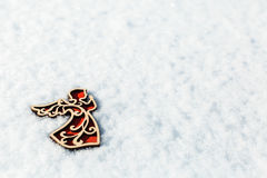 Red wooden toy angel on snow Stock Photos