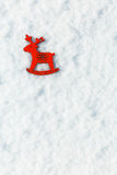 Red wooden toy deer in the snow Royalty Free Stock Photo