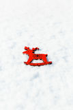 Red wooden toy deer in the snow Royalty Free Stock Photography