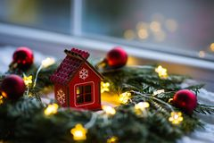 Red wooden toy house surrounded with fir-tree wreath decorated with warm garland lights and little Christmas balls near window. New Year festive glowing stock photo