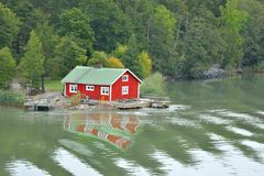 Red wooden traditional Finnish house and pier on bank of island stock photo