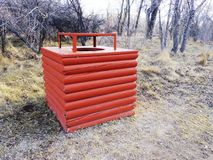 Red wooden trashcan. A red wooden trashcan along a trail in the woods Stock Photography