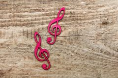 Red wooden treble clef on wooden background, stock photography