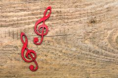 Red wooden treble clef on wooden background, stock image