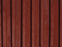Red wooden wall. Scandinavian wooden boarded wall painted with traditional falu red paint Stock Image