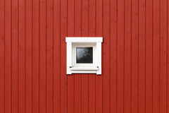 Red wooden wall with small window in white frame Stock Photo