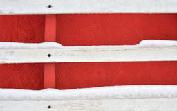 The red wooden wall with three white scratched planks with nail on wood. On the planks a snow. Place for design and text. Abstract background Stock Images