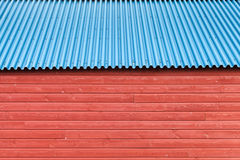 Red wooden wall under blue metal roof. Background photo texture Royalty Free Stock Photo