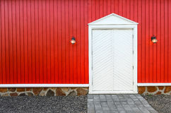 Red wooden wall and white front doors with two lamps Stock Photography