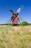 Red wooden windmill on the summer field. Idyllic landscape with traditional old Swedish windmill Stock Images