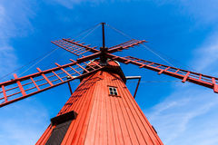 Red wooden windmill. Swedish red painted windmill against the blue sky Stock Photo