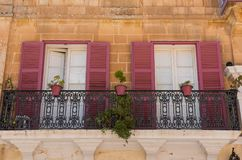 Red wooden window shutters on a house. Red wooden window shutters on a stone house. Mdina, Malta Stock Image