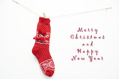 Red wool Christmas socks on white. Red wool Christmas socks hanging on the white wall Stock Photo