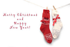 Red wool Christmas socks on white. Two pairs of wool Christmas socks, red and white, hanging on the white wall Royalty Free Stock Images