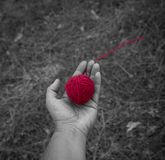 Red wool clew in human hand, top view stock photo