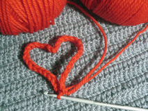 Red wool clews and knitted heart Stock Image