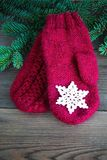 Red wool mittens with wiht cotton crocheted snowflake near green christmas fur tree on the rustic wooden background. Toned. Christ stock image