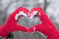 Red woolen glooves making a heart shape in snow Royalty Free Stock Photography